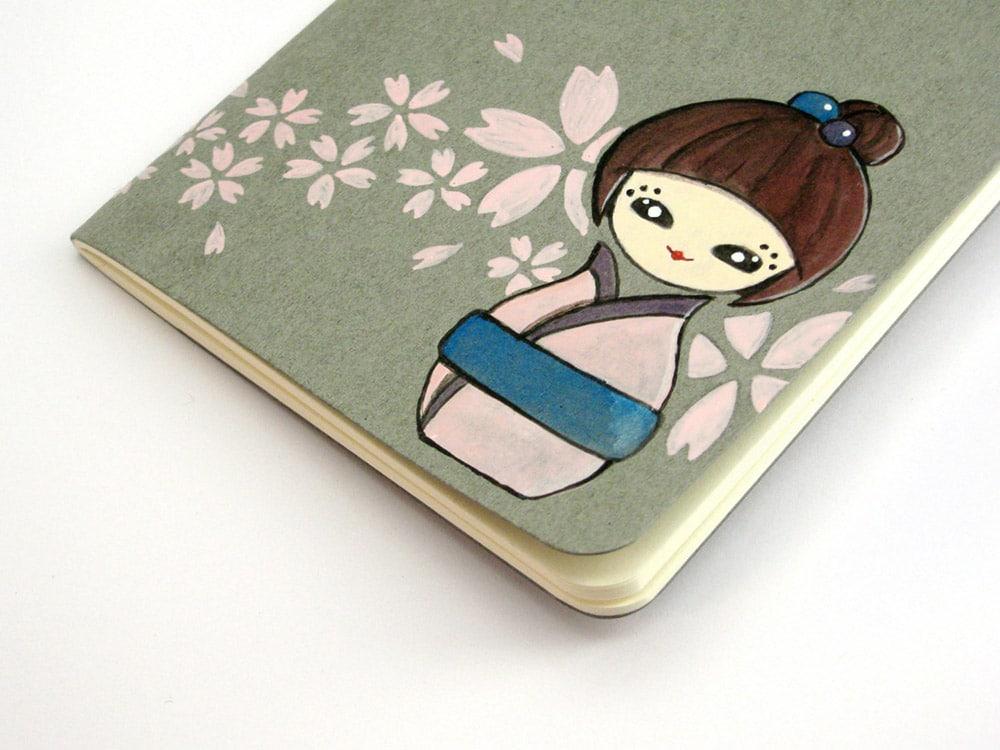 Quaderno con disegnata a mano una bambolina kokeshi